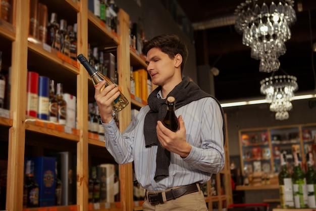 Niedriger winkelschuss eines hübschen jungen eleganten mannes, der wein wählt, um am supermarkt zu kaufen