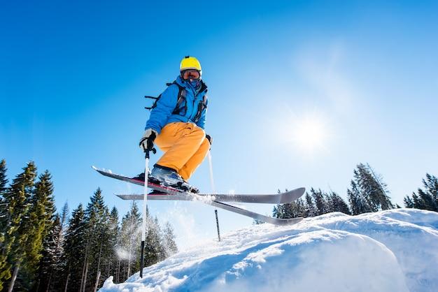 Niedriger winkelschuss eines skifahrers in der bunten ausrüstung, die beim skifahren auf einer piste in die luft springt