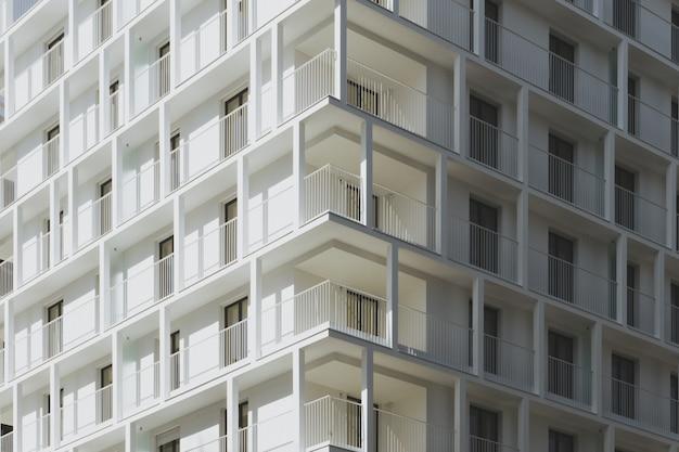 Niedriger winkelschuss eines weißen betongebäudes, das zur tageszeit gefangen genommen wird