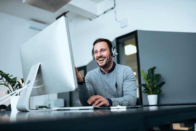 Niedriges winkelbild des glücklichen zufälligen geschäftsmannes, der an computer mit kopfhörer arbeitet.