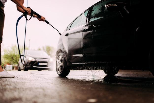 Niedriges winkelbild einer person, die ein auto mit hochdruckstrahl wäscht.