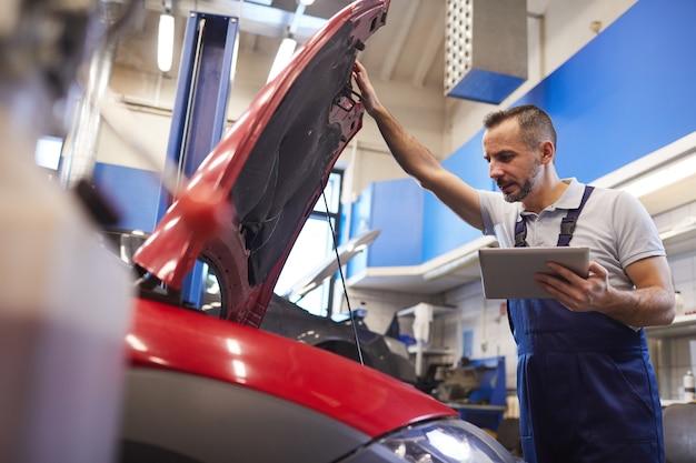 Niedriges winkelporträt des bärtigen automechanikers unter verwendung des digitalen tabletts und der sich öffnenden haube während der fahrzeuginspektion im garagengeschäft, kopierraum