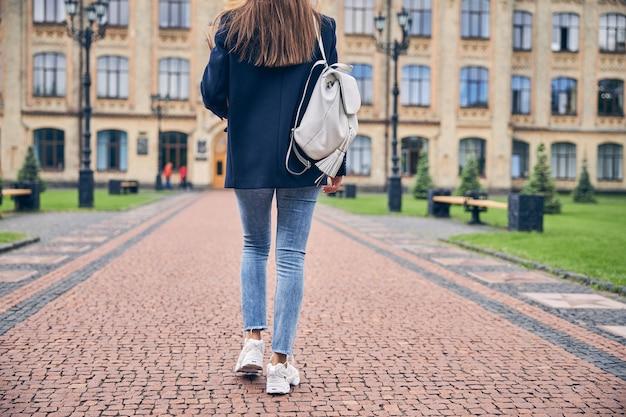 Niedrigwinkelfoto einer brünetten frau mit rucksack in freizeitkleidung, die allein zur universität geht