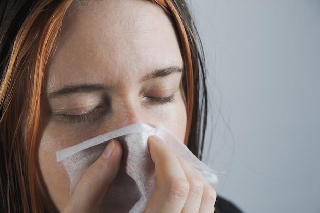 Niesen, husten oder nase putzen in einem einweg-papiertuch. konzept, erkältung, virus oder infektion zu fangen und nicht zu verbreiten