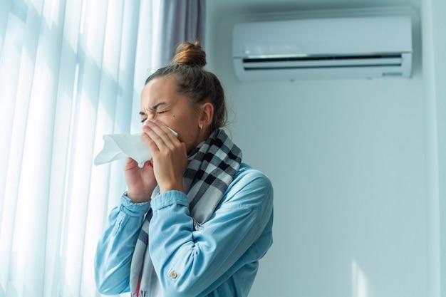 Niesende frau erkältet sich von der klimaanlage zu hause. conditioner krankheit