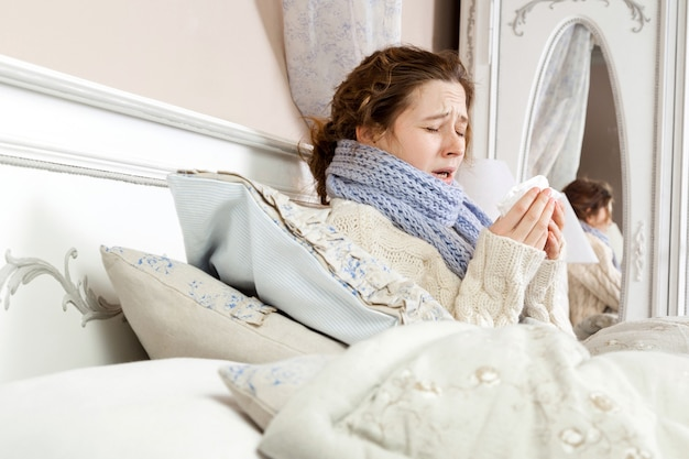 Niesende schönheit. junge kranke frau mit blauem schal um den hals, die im bett sitzt und auf ihrem bett niest.
