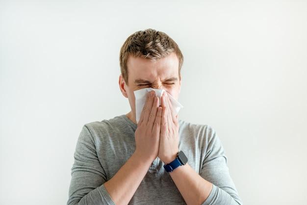Niesender mann im taschentuch, der die laufende nase abwischt, symptome einer ansteckenden atemwegserkrankung, coronavirus- und grippesymptome