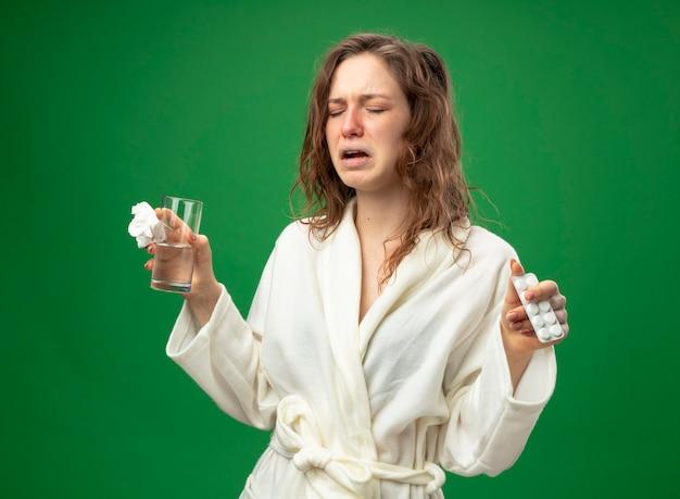 Niesendes junges krankes mädchen, das weißes gewand trägt, das glas wasser mit den auf grün lokalisierten pillen hält