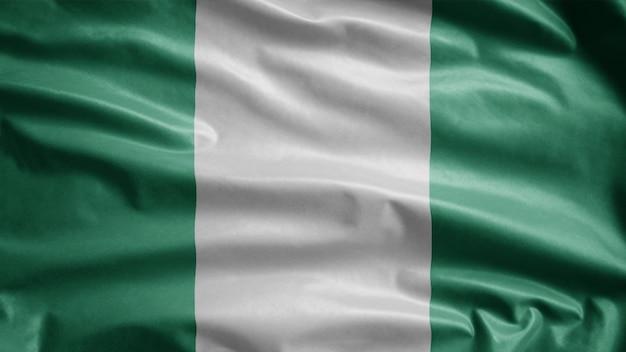 Nigerianische flagge, die im wind weht. nahaufnahme von nigeria vorlage bläst, weiche und glatte seide. stoff stoff textur fähnrich hintergrund. verwenden sie es für das konzept des nationalfeiertags und der länderanlässe