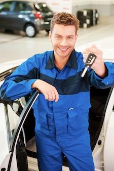 Nimm dein auto. fröhlicher junger mann in uniform, der die hand mit schlüsseln ausstreckt, während er in der werkstatt in der nähe des autos steht