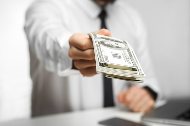 Nimm dein geld! porträt von richman investor big boss in weißem hemd und schwarzer krawatte sitzen im büro und geben ihnen viel geld, ihren bonus, isoliert, indoor, fokus, studioaufnahme,
