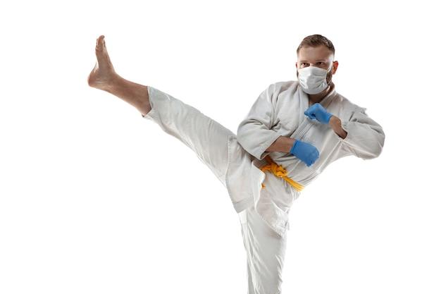 Nimm die korona ab. kampfkunstkämpfer in schutzmaske, handschuhen. auch während der quarantäne aktiv. gesundheitswesen, medizin, sportkonzept.