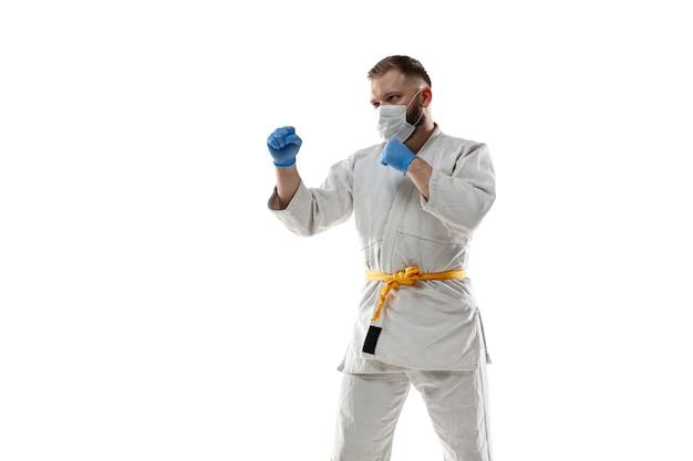 Nimm die korona ab. kampfkunstkämpfer in schutzmaske, handschuhen.