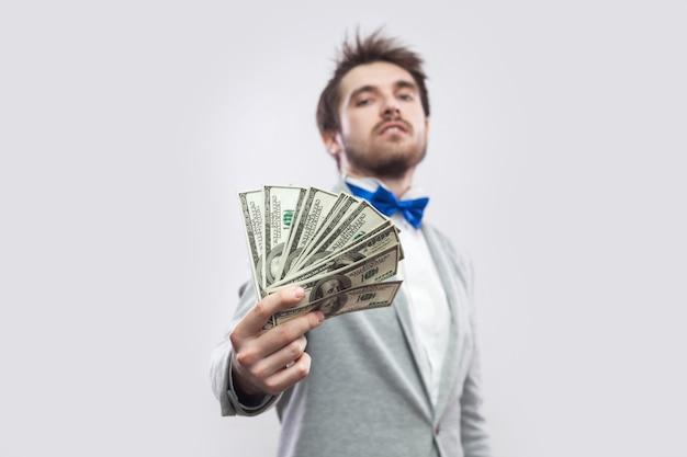 Nimm es! porträt eines selbstbewussten, attraktiven jungen geschäftsmannes in grauem mantel und blauer fliege stehend, stolz mit erhobenem kopf und gibt ihnen viele dollar. innen, studioaufnahme, isoliert, grauer hintergrund.