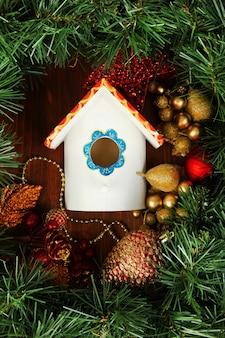Nistkasten und weihnachtsschmuck auf holzuntergrund