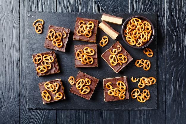 No-bake-schokoladen-erdnussbutterriegel mit brezelcrackern auf einem schiefertablett auf einem holztisch, blick von oben, flatlay, freiraum