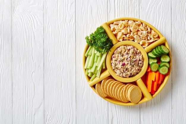 No-cook thunfisch kapern gurken aufstrichset serviert mit karotten und selleriestangen, geschnittener frischer gurke, crackern und schwarten in schalen auf einem weißen holztisch, philippinen-stil, flach gelegt, freiraum