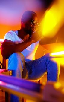 Nobel. filmisches porträt eines stilvollen jungen mannes im neonbeleuchteten raum. helle neonfarben. afroamerikanisches modell, musiker drinnen. jugendkultur im party-, festival- und musikkonzept.