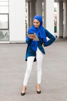 Nobler teenager mit hijab, der auf ihrem tablett schaut