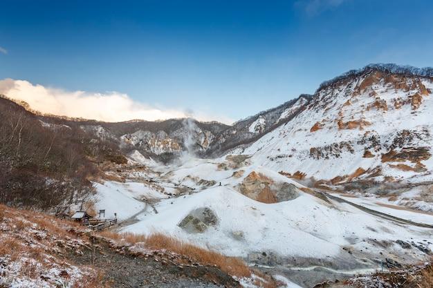 Noboribetsu jigokudani, hokkaido, japan in der wintersaison mit dem strahlend blauen himmel, schwefelgasdampf aus dem boden