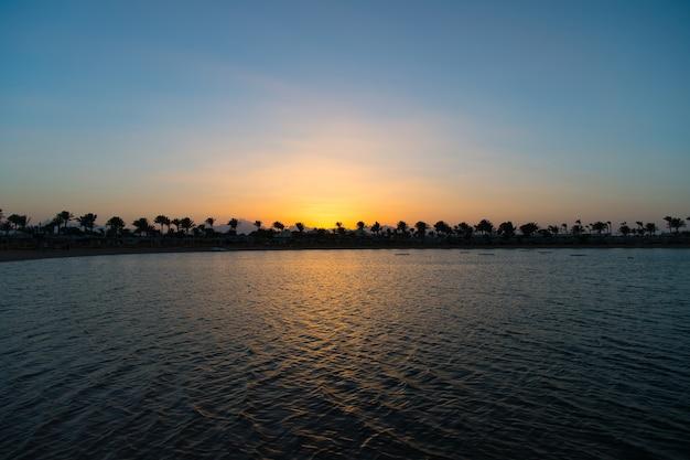 Noch ein perfekter sonnenuntergang. sonnenuntergang am meer mit palmen und sonnenreflexionswasser. schattenbild des tropischen inselparadiesabends der palmen. genießen sie den paradiesischen schönheitssonnenuntergang im tropischen strandresort.