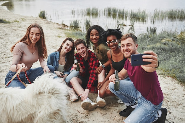 Noch ein selfie. eine gruppe von menschen hat ein picknick am strand. freunde haben spaß am wochenende.