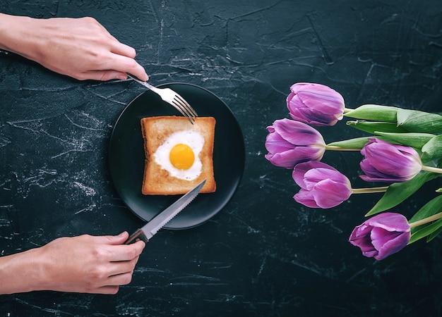 Noch frühstück für einen geliebten menschen mit tulpen auf dunklem hintergrund