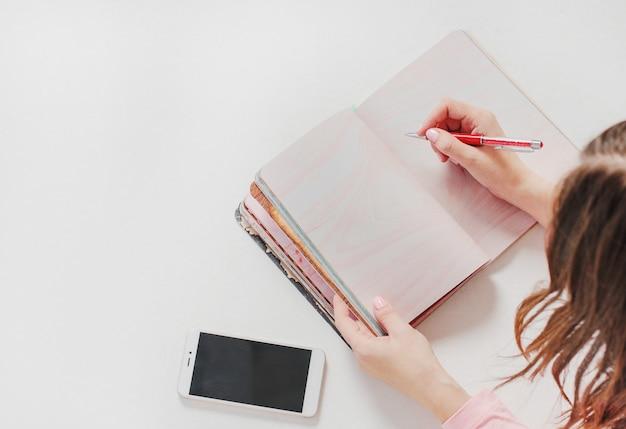 Noch leben mit offenem planernotizbuch, frauenhänden mit stift und