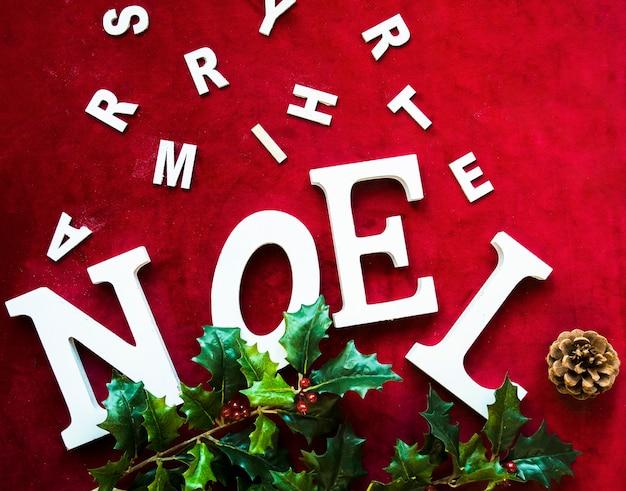 Noel-titel in der nähe von baumstumpf, buchstaben und grünem zweig