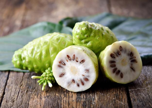 Noni-frucht auf hölzernem hintergrund