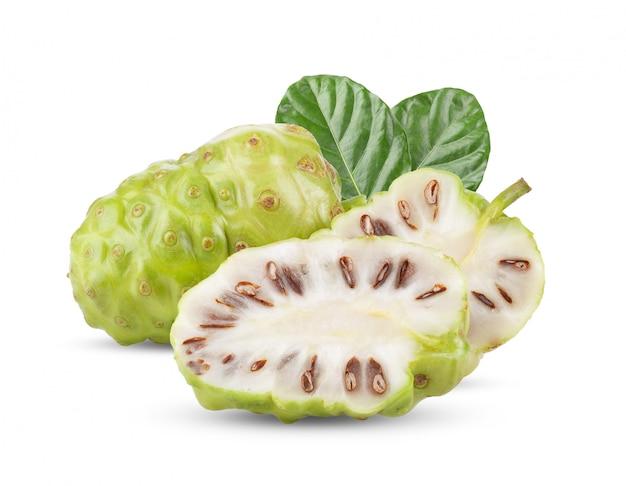 Noni-frucht mit blättern auf weißem tisch.
