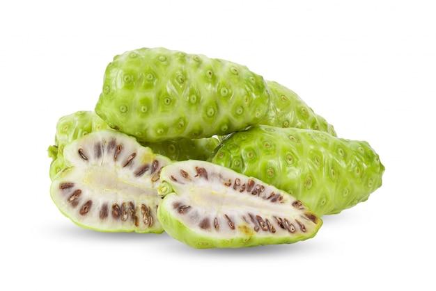 Noni-frucht mit blättern auf weißer wand.