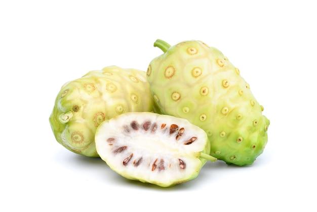 Noni- oder morinda citrifolia-früchte mit geschnittenem lokalisiertem weißem hintergrund