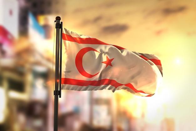 Nord-zypern-flagge gegen stadt verschwommen hintergrund bei sonnenaufgang hintergrundbeleuchtung