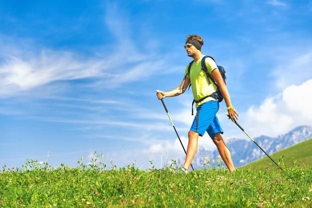 Nordic walking mit stöcken in der natur in den hügeln