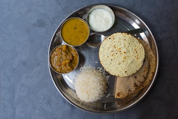Nordindisches thali, eine tipical mahlzeit diente auf edelstahlplatte auf blauer tabelle