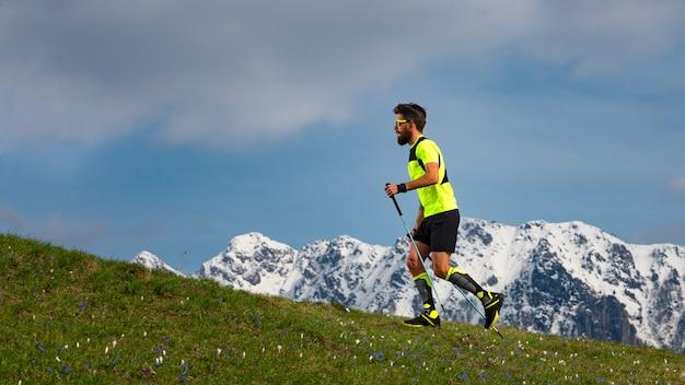 Nordisches gehen und trailrunning eines mannes mit stöcken auf frühlingsbrasse mit schneebedecktem hintergrund