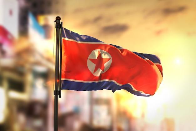 Nordkorea-flagge gegen stadt verschwommener hintergrund bei sonnenaufgang-hintergrundbeleuchtung