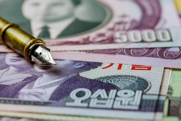 Nordkoreaner von verschiedenen banknoten geld gewann geldschein über stift zum schreiben