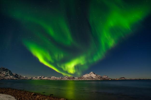 Nordlichter, aurora borealis mit bergen im hintergrund über senja, norwegen