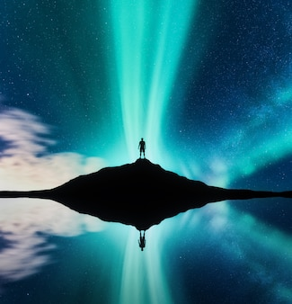 Nordlichter und silhouette des stehenden mannes im hügel in norwegen. aurora borealis und mensch. sterne und grüne polarlichter.