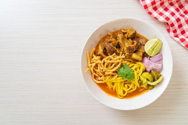 Nordthailändische nudel-curry-suppe mit geschmortem schweinefleisch nach thailändischer art