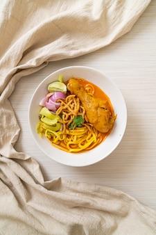 Nordthailändische nudel-curry-suppe mit hühnchen (kao soi kai). thailändischer essensstil
