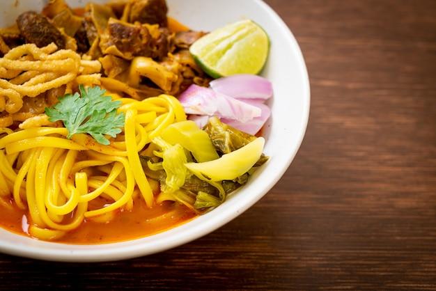 Nordthailändische nudelcurrysuppe mit geschmortem schweinefleisch - thailändischer essensstil