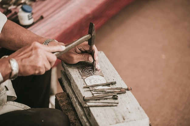 Nordthailändisches älterer künstler handcraft schnitzersilber mit hammer und meißel für silbernes kunsthandwerk der kulturart bei chiang mai, thailand.