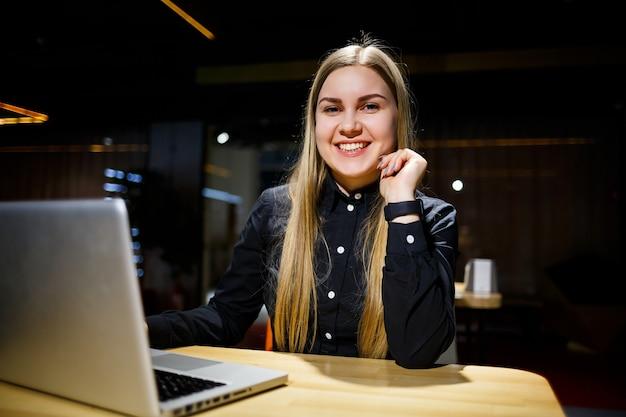 Normaler arbeitstag des modernen frauengeschäftsmannes. schöne junge frau, die an einem laptop arbeitet, während sie an ihrem arbeitsplatz sitzt