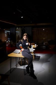Normaler arbeitstag des modernen frauengeschäftsmannes. schöne junge frau, die eine tasse kaffee hält, während sie an ihrem arbeitsplatz sitzt