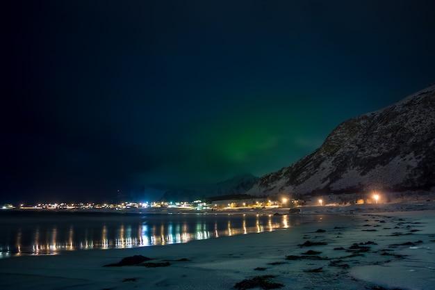 Norwegen. lofoten. ein kleines dorf in der nähe des berges am ufer des fjords. winternacht