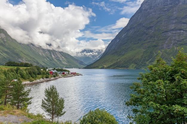 Norwegischer fjord und berge, umgeben von wolken, ideale fjordreflexion in klarem wasser.