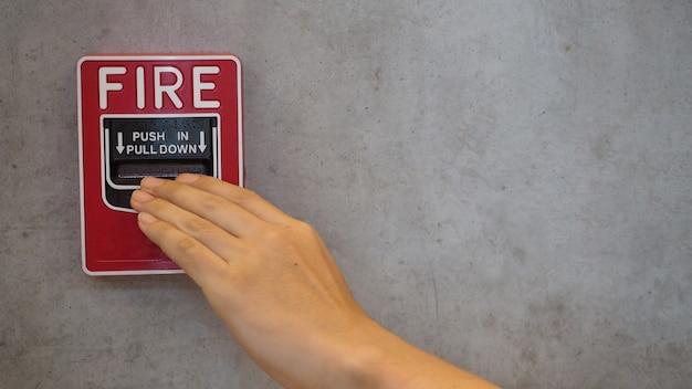 Not-feueralarm oder alarm- oder klingelwarnausrüstung in roter farbe mit hand im gebäude zur sicherheit.